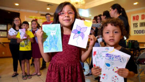 Los hermanos Lily (7 años) y Benji (5) posan con las cartas que escribieron a los nuevos niños albergados en los centros de detención del Servicio de Inmigración y Aduanas (ICE) este 19 de julio de 2018, en la sede del centro jurídico Formación para el Desarrollo Ocupacional de las Comunidades Educativas (TODEC) en Perris, California (Estados Unidos). Foto. EFE