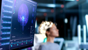 Woman Wearing Brainwave Scanning Headset Sits in a Chair In the Modern Brain Study Laboratory/ Neurological Research Center. Photo: Shutterstock