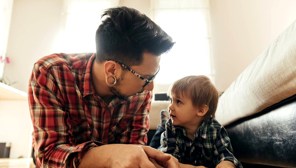Father and son lying on the floor with a book — Stock Photo.