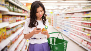 Young woman reading information about the product on the phone. Photo: DragonImages.