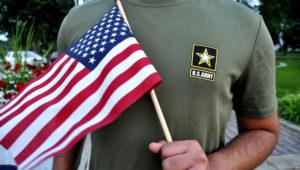 Un recluta pakistaní, de 22 años, quien recientemetne fue dado de baja del Ejército de EE.UU., sostiene una bandera estadounidense mientras posa para una fotografía, julio, 3, 2018.