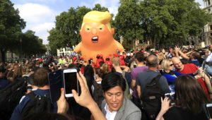 """A protest against President Trump in London's Parliament Square includes a giant balloon of """"Trump Baby"""" in a diaper on Friday. It flew high above the statutes of prominent historical figures including Winston Churchill, Mahatma Gandhi and Millicent Fawcett. AMER GHAZZAL / BARCROFT MEDIA VIA GETTY IMAGES"""
