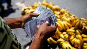A street vendor counts bolivar notes as he waits for clients in Caracas, Venezuela March 23, 2018. REUTERS/Carlos Garcia Rawlins