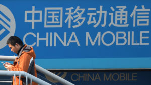 A man uses his mobile phone as he walks past a China Mobile sign on a street in Shanghai on December 23, 2013. AFP PHOTO/Peter PARKSPETER PARKS/AFP/Getty Images