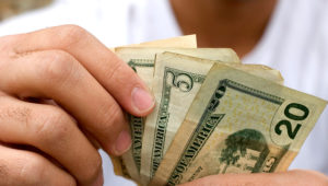 Money counting, young adult. JASON STITT VIA GETTY IMAGES