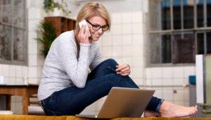 Mujer joven que trabaja desde su casa sentado descalzo en un mostrador de la cocina hablando por su móvil mientras se lee la pantalla de su ordenador portátil en equilibrio sobre el respaldo del sofá. Foto: 123rf.com