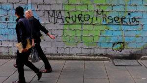 """Dos personas caminan este sábado en Caracas por delante de una pintada en la que se lee """"Maduro, Miseria"""". REUTERS / EPV"""