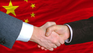 Businessmen handshake after good deal in front of China flag — Stock Photo
