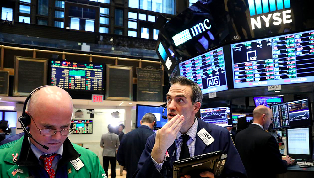 Traders work on the floor of the New York Stock Exchange (NYSE) as the Dow Jones industrial average closed above the 20,000 mark for the first time on January 25 in New York City. SPENCER PLATT/GETTY