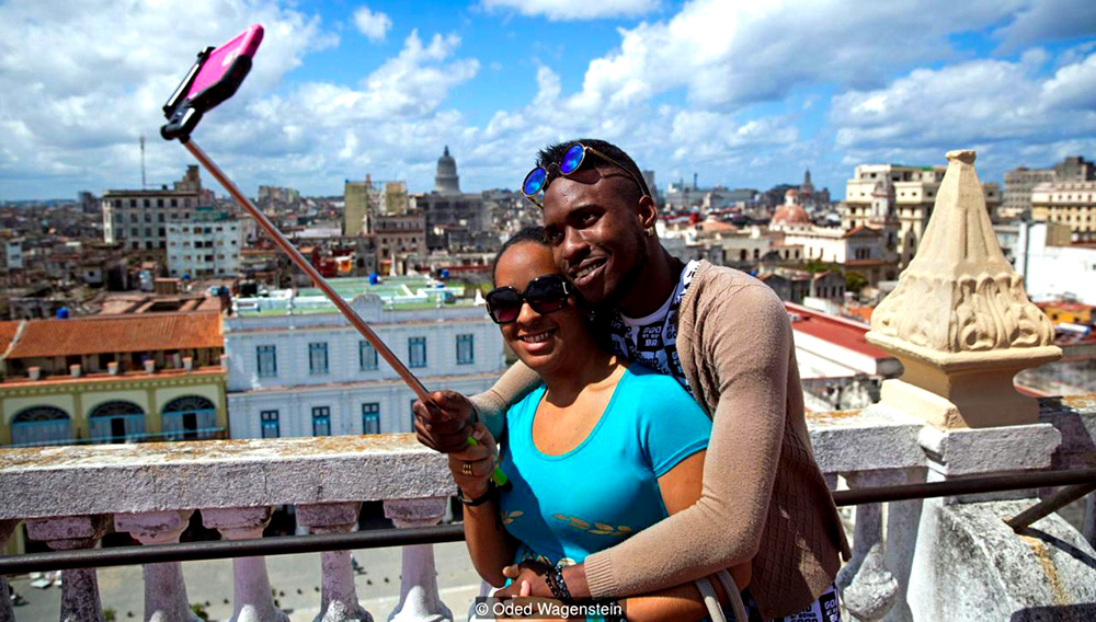 A local couple takes a selfie on a rooftop in Old Havana. In the background is El Capitolio, an almost identical twin to the US Capitol building in Washington DC. (Credit: Oded Wagenstein)