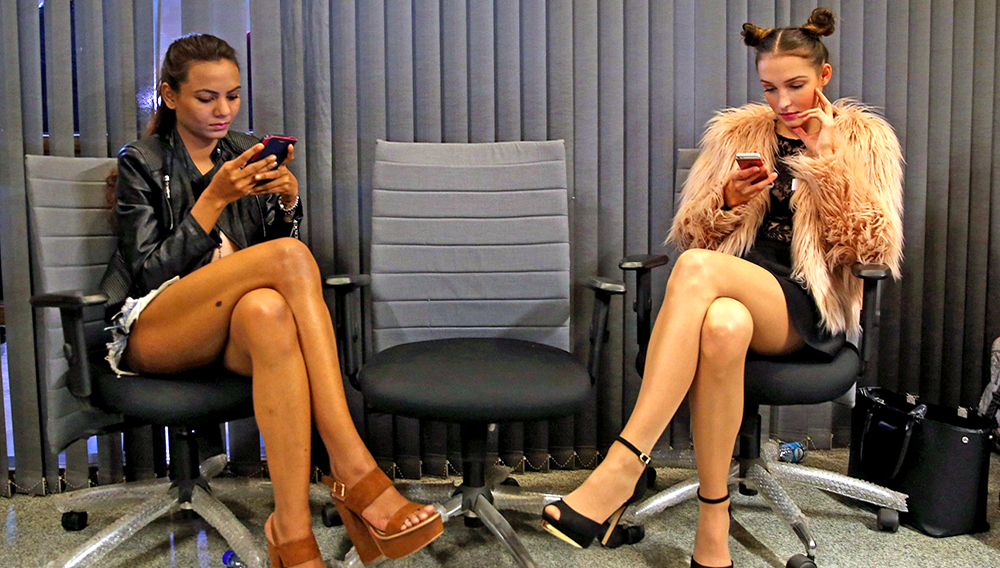 Models use their mobile phones as they wait during an audition for the Amazon India Fashion Week Fall/Winter 2017 in New Delhi, India, 19 January 2017. The fashion eweek will kick off on 15 March. EPA/RAJAT GUPTA