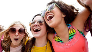 Portrait of a group of teenage girls laughing. COMPASSIONATE EYE FOUNDATION/RENNIE SOLIS VIA GETTY IMAGES