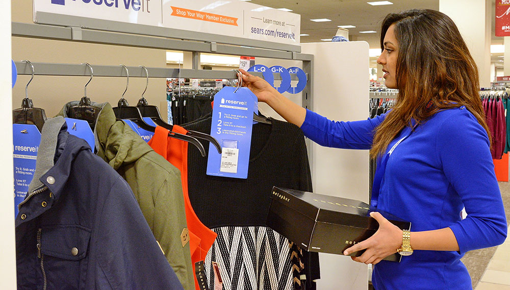A Sears associate stocks the Reserve It rack with customer merchandise requests made through Shop Your Way. Items are reserved for 48 hours. (PRNewsFoto/Sears, Roebuck and Co.)