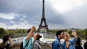 Dos parejas de jóvenes tomándose selfis con la torre Eiffel como paisaje de fondo.
