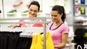 Dos mujeres jóvenes para compras de ropa en la tienda de deportes. Fotostock: Alamy.es