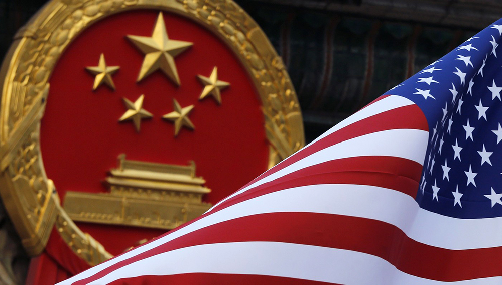 An American flag is flown next to the Chinese national emblem during a welcome ceremony for visiting U.S. President Donald Trump CREDIT: AP