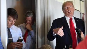 El subsecretario de prensa de la Casa Blanca Hogan Gidley (izquierda) y el subjefe del equipo de comunicación de la Casa Blanca Bill Shine (al centro) escuchan mientras el presidente Donald Trump habla con reporteros en un vuelo desde Billings, Montana, a Fargo, Dakota del Norte, el viernes 7 de septiembre de 2018. (AP Foto/Susan Walsh)
