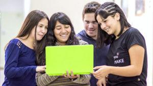 Jóvenes estudiantes observando sonrientes una laptop de escuela. Foto: Virtual Educa