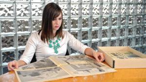Mujer millennial leyendo un periódico.