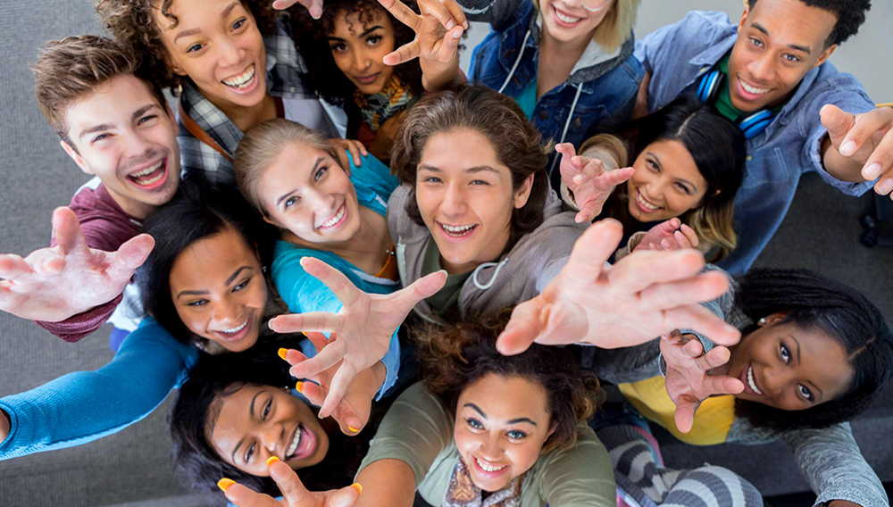 High angle view of group of college students reaching up. Excited diverse male and female college students celebrate the end of the semester. They are reaching up toward the camera. Getty Images