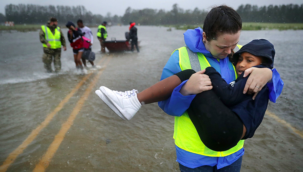 Volunteers from the Civilian Crisis Response Team help rescue three children from their flooded home September 14, 2018 in James City, United States.