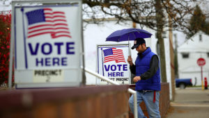 A man fills walks past voting signs displayed outside a polling station during the mid-term elections November 4, 2014 in Hamtramck, Michigan. Getty Images.
