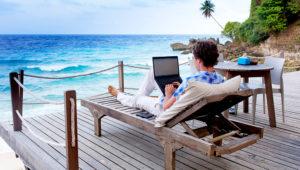 Joven usando una laptop en un lugar con vista al mar. Foto: Shutterstock