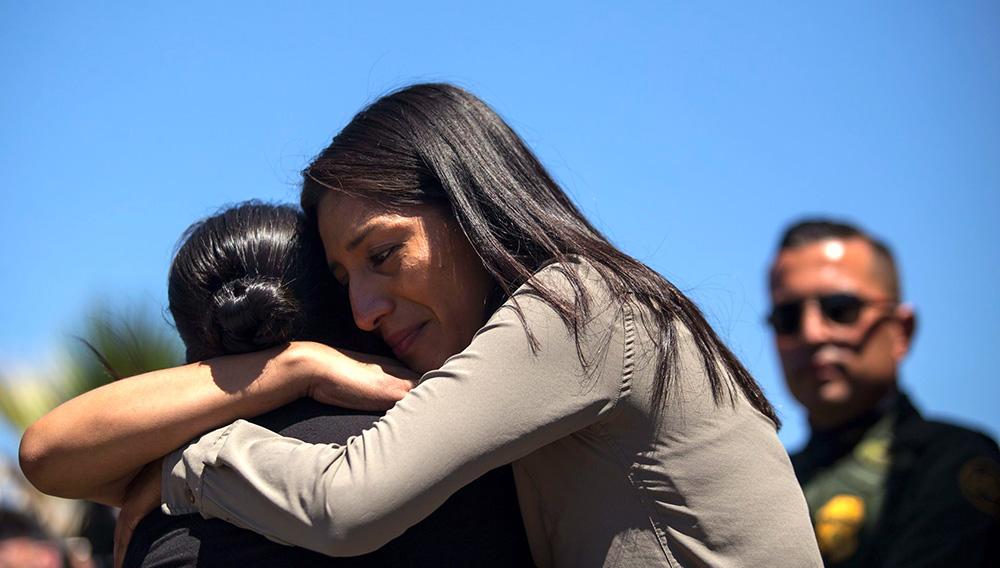Miembros de la familia Lorenzo Mosso viven en diferentes lados de la frontera y se reunieron brevemente en la esquina frontereiza de Playas de Tijuana. (GUILLERMO ARIAS / AFP/Getty Images)