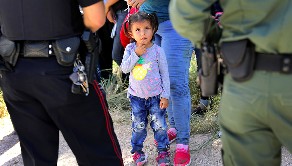 A Mission Police Dept. officer (L), and a U.S. Border Patrol agent watch over a group of Central American asylum seekers before taking them into custody on June 12, 2018 near McAllen, Texas John Moore—Getty Images