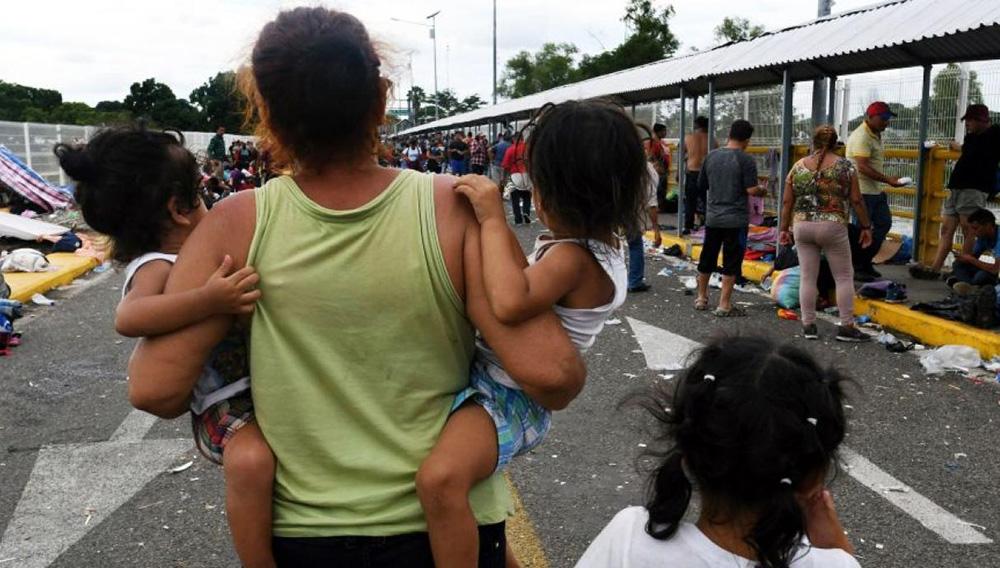 Migrantes hondureños comienzan a adentrarse en México por la frontera con Guatemala, tras romper la valla metálica en medio de un dispositivo de policías, agentes de migración y organismos de derechos humanos.