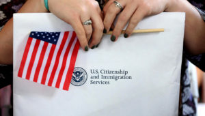 HOMESTEAD, FL - FEBRUARY 17: A newly sworn in United States citizen holds her paperwork during a naturalization ceremony put on by the U.S. Citizenship and Immigration Services at the Biscayne National Park on February 17, 2015 in Homestead, Florida. The ceremony saw roughly 150 people, primarily children, sworn in from countries around the globe such as China, Philippines and Cuba. among others. (Photo by Joe Raedle/Getty Images)