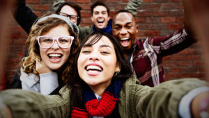 Five young friends grin take a happily smiling 'selfie' or self-portrait on a cellphone, while standing outside by a brick wall. GETTY IMAGES