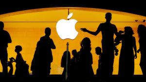 Customers walk past an Apple logo inside of an Apple store at Grand Central Station in New York, U.S., August 1, 2018. REUTERS/Lucas Jackson