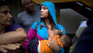 Madeley Vásquez, de 16 años, da el pecho a su hijo de uno Joangel mientras espera en el exterior de un supermercado para comprar comida en Caracas, Venezuela. Foto de AP.