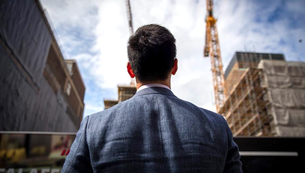 Hombre joven de espaldas a la cámara, mirando de lejos a unos edificios.