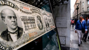 People walk past a bank's branch decorated with images of old Argentine peso bills, in Buenos Aires, on September 26, 2018. - A crisis of confidence beginning in April saw the value of the peso plunge, with Argentina negotiating its $50 billion bailout loan from the IMF. The central bank hiked interest rates to a world-high 60 percent and the peso has remained largely stable since its sudden crash in August. (Photo by EITAN ABRAMOVICH / AFP)