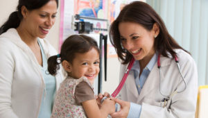 Toddler girl laughing while doctor examines