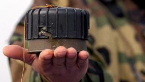 Close up de la mano de un soldado sosteniendo una mina antipersona.