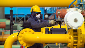 A worker makes an adjustment at a Repsol-YPF gas plant in Loma de la Lata, Neuquen province, Patagonia Argentina, Friday, May 13, 2005. The plant processes and compacts gas sending it through a 900-mile long pipeline to the city of Buenos Aires. Photographer Diego Giudice/Bloomberg News