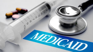 Medicaid, health concept. Stethoscope, syringe and pills on grey background. Shutterstock