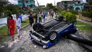 Un vehículo volteado por la fuerza de un tornado en una calle de La Habana, Cuba, el lunes 28 de enero de 2019. Un tornado y fuertes lluvias azotaron el este de la capital cubana la madrugada del lunes derribando árboles y doblando postes de luz. (AP Foto/Ramon Espinosa)