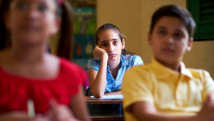 Young people and education. Group of hispanic students in class at school during lesson. Girl with anxiety, bored female student