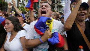 Anti-government protesters cheer as Juan Guaido, head of Venezuela's opposition-run congress, declares hi interim president of the South American country until a new election can be called, at a rally demanding the resignation of President Nicolas Maduro in Caracas, Venezuela. (AP Photo/Boris Vergara)