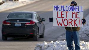 Un trabajador de la Agencia de Protección Ambiental de EEUU (EPA, por sus siglas en inglés) afectado por el cierre parcial del gobierno protesta con un cartel ante las oficinas del senador Mitch McConnell, en Park Hills, Kentucky, el 22 de enero de 2019. (AP Foto/Bryan Woolston)