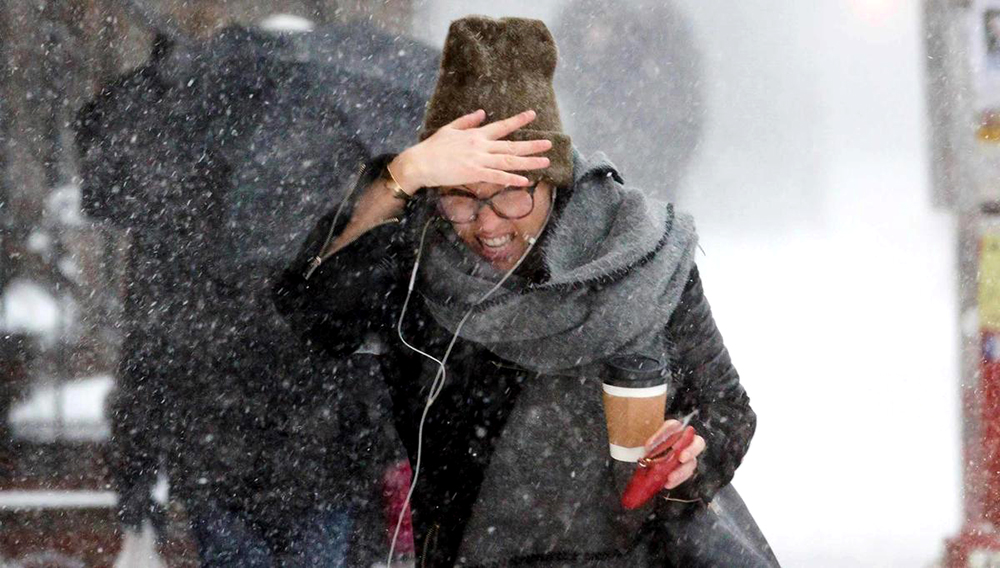 A woman shields herself from snow and wind during a winter storm in Brooklyn, N.Y., on Jan. 4, 2018.