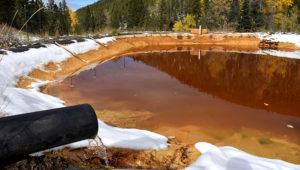 En esta foto del 12 de octubre de 2018, agua contaminada con arsénico, plomo y zinc sale de un caño de la mina Lee Mountain a un estanque de retención cerca de Rimini, Montana. (AP Foto/Matthew Brown)