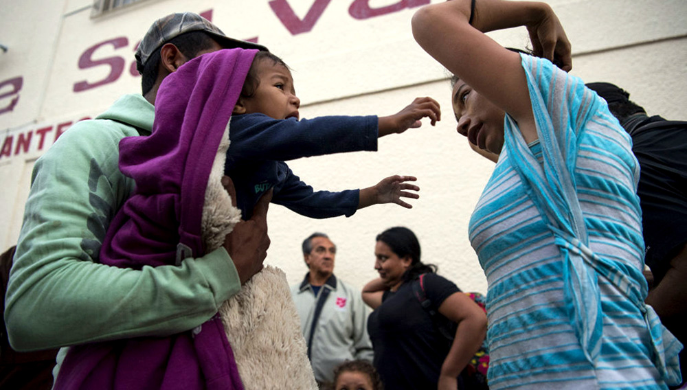 TIJUANA, MEXICO - APRIL 26: Javier Rivera holds his son Alexander, 1, as his partner Maria Angelica Garcia Garcia fixes her hair at the Ejercito de Salvacion shelter on April 26, 2018 in Tijuana, Mexico. (Photo by Carolyn Van Houten/The Washington Post via Getty Images)