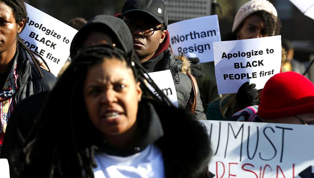 Manifestantes sostienen letreros y corean lemas frente a la casa del gobernador en Richmond, Virginia, el sábado 2 de febrero de 2019. Los manifestantes piden la renuncia del gobernador de Virginia Ralph Northam después de que una foto de hace 30 años de él fue distribuida ampliamente el viernes. (Foto AP/Steve Helber)