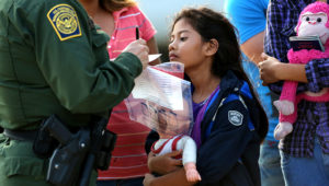 Salvadorian immigrant Stefany Marjorie, 8, watches as a U.S. Border Patrol agent records family information on July 24, 2014 in Mission, Texas. John Moore / Staff   Getty Images News