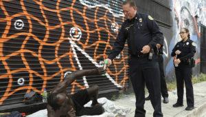 El agente James Bernat de la policía de Miami entrega un repelente de insectos a un hombre indigente, el martes 2 de agosto de 2016 en el barrio Wynwood, en Miami. (AP Foto/Lynne Sladky) (Lynne Sladky / AP)